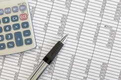depositphotos_6315045-Calculator-and-pen-on-spreadsheet